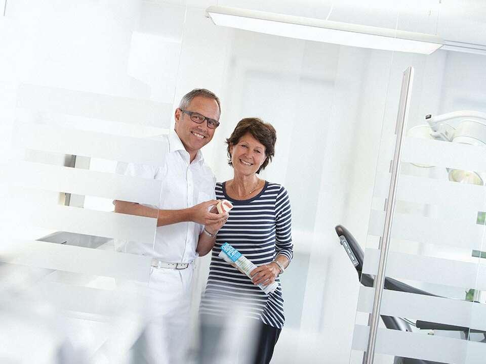 Dr. Ralf Quirin erklärt einer Patientin in der Zahnarztpraxis die Behandlung von Parodontitis