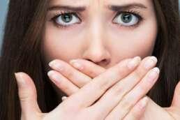 Junge Frau versteckt ihre Zähne